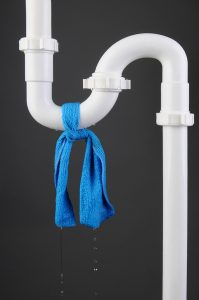 white pvc pipe with blue cloth tied around it