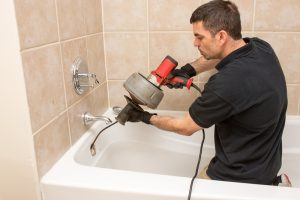plumber-unclogging-drain-with-drain-snake