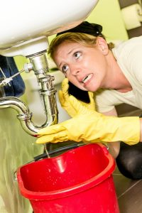 woman-looking-worried-about-plumbing-problem-under-sink