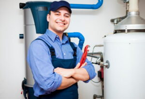 smiling-technician-standing-in-front-of-water-heater-and-holding-wrench