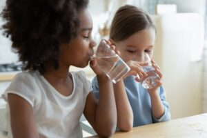 two-girls-drinking-water-from-glasses